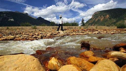 Silverton resident Melanie Bergolc walks along the banks of Cement Creek in Silverton, Colo., Monday, Aug. 10, 2015. The area is a few miles downstream from the Gold King mine, where a wastewater accident several days earlier allowed yellow water contaminated with heavy metals to pour into the creek that feeds rivers critical to survival on the largest Native American reservation in the United States and across the Southwest. (Jon Austria /The Daily Times via AP)