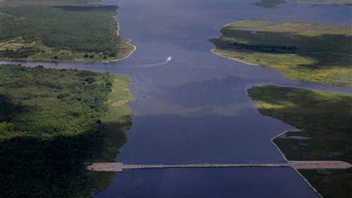 In this aerial photo made during a flight provided by the National Wildlife Federation and Southern Wings, a shrimp boat travels behind a rock dam built by the U.S. Army Corps of Engineers after Hurricane Katrina, in the Mississippi River Gulf Outlet (MRGO) in St. Bernard Parish, La., Monday, Aug. 10, 2015. The MRGO, originally built by the Corps, carried a storm surge from Katrina straight into the New Orleans area causing devastating flooding in the Parish. (AP Photo/Gerald Herbert)