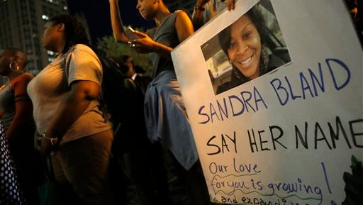 A demonstrator holds a Sandra Bland sign during a vigil, Tuesday evening, July 28, 2015,  near the DuSable Bridge on Michigan Ave. in Chicago. Bland died in a Texas county jail after the traffic stop for failing to use a turn signal escalated into a physical confrontation. Authorities have said Bland hanged herself, a finding her family disputes. The death has garnered national attention amid increased scrutiny of police treatment of blacks in the wake of several high-profile police-involved deaths.