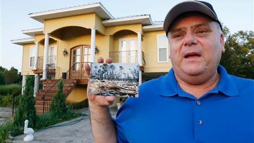 In this July 23, 2015 photo, Efrem Garza stands before his new home built on the lot of his previous house that was destroyed by Hurricane Katrina and holds a photograph taken by a friend of the remains of that house on South Seashore Avenue in Long Beach, Miss. Before the storm Garza was surrounded by houses and trees, now 10 years later, there are only two houses on that land, as few of the residents returned and rebuilt. (AP Photo/Rogelio V. Solis)