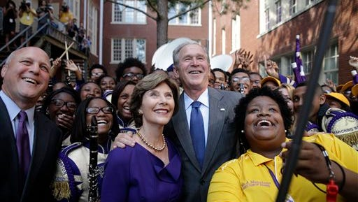 Former President George W. Bush poses for a 'selfie' photo with former first lady Laura Bush, marching band director Asia Muhaimin, right, and New Orleans Mayor Mitch Landrieu, far left, at Warren Easton Charter High School in New Orleans, Friday, Aug. 28, 2015. Bush is in town to commemorate the 10th anniversary of Hurricane Katrina, which is Saturday. (AP Photo/Gerald Herbert)