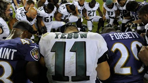 FILE - In this Aug. 22, 2015, file photo, Philadelphia Eagles' Tim Tebow prays after a preseason NFL football game against the Baltimore Ravens in Philadelphia. Two people familiar with the move say the Eagles released Tebow. Both sources spoke on condition of anonymity, Saturday, Sept. 5, 2015, because the team hasn't announced the decision. (AP Photo/Michael Perez, File)