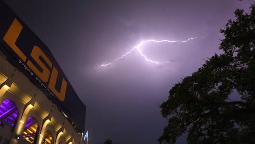 Lightning bolts are seen over Tiger Stadium during a weather delay at an NCAA college football game between LSU and McNeese State in Baton Rouge, La., Saturday, Sept. 5, 2015. The game was canceled due to weather. (AP Photo/Jonathan Bachman)