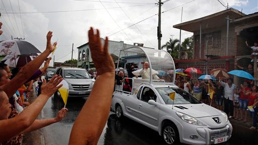 Pope Francis greets people from his popemobile on his way to the Hill of the Cross in Holguin, Cuba, Monday Sept. 21, 2015. Francis ended his time in Holguin by blessing Cuba's fourth-largest city from the Hill of the Cross, a pilgrimage site overlooking the city. (AP Photo/Enric Marti)