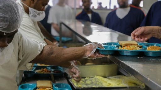 Prisoners supervised by Aramark serve meals at a Jackson-area prison.