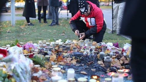 A man lights a candle outside Kronan school in Trollhattan, Friday, Oct. 23, 2015, a day after an attack. The attacker who stabbed two people to death at the school before being shot and killed by police had a racist motive, police said. (Adam Ihse/TT News Agency via AP) SWEDEN OUT