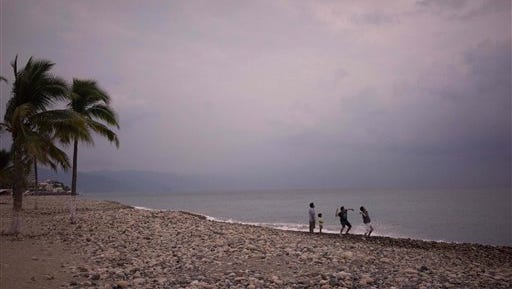 People throw stones into the ocean as hurricane Patricia nears in the Pacific resort city of Puerto Vallarta, Mexico, Thursday, Oct. 22, 2015. Hurricane Patricia grew into a monster, Category 5 storm and bore down on Mexico's central Pacific Coast, on or near Puerto Vallarta, on Thursday night for what forecasters said could be a devastating blow, as officials declared a state of emergency and handed out sandbags in preparation for flooding. (AP Photo/Cesar Rodriguez)
