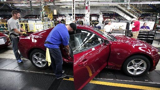 Workers put the finishing touches on a 2016 Chevrolet Camaro as it rolls off the production line at GM's Lansing Grand River Assembly Plant last month.