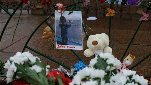A portrait of 10-month-old Darina Gromova, a victim of a plane crash, is surrounded by flowers and toys attached to a fence at Dvortsovaya (Palace) Square in St.Petersburg, Russia, Wednesday, Nov. 4, 2015. A Russian official says families have identified the bodies of 33 victims killed in Saturday's plane crash over Egypt. The Russian jet crashed over the Sinai Peninsula early Saturday, killing all 224 people on board. Most of them were holidaymakers from Russia's St. Petersburg.