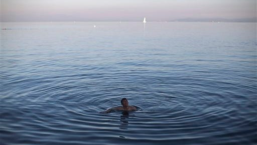 An Afghan man swims in the Aegean sea as he waits for a ferry to transport him to Athens in the port of Mytilene, on the island of Lesbos, Greece, Wednesday, Nov. 4, 2015. Thousands of migrants and refugees are stranded on Lesbos due to a ferry strike that began Monday. (AP Photo/Marko Drobnjakovic)