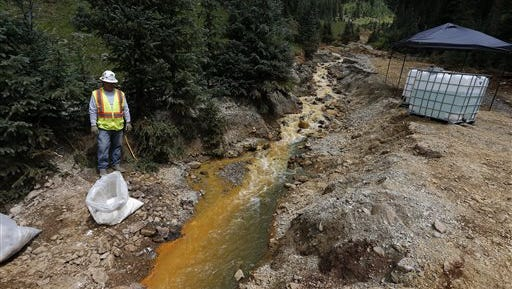 In this Aug. 12, 2015 photo, an Environmental Protection Agency contractor keeps a bag of lime on hand to correct the PH of mine wastewater flowing into a series of sediment retention ponds, part of danger mitigation in the aftermath of the blowout at the site of the Gold King Mine, outside Silverton, Colo.  Colorado officials are disputing a key claim by federal agencies about a massive spill of toxic wastewater from an inactive mine. A report by the federal Bureau of Reclamation, said two state mining experts signed off on an Environmental Protection Agency cleanup project that led to the Aug. 5 spill at the Gold King Mine in southwest Colorado. (AP Photo/Brennan Linsley)