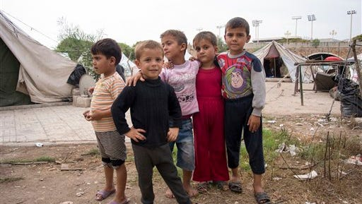 "In this photo taken on Friday, Oct.  23, 2015, Children stand at a refugee camp in Latakia, Syria. Latakia, the heartland of Syrian President Bashar Assad's Alawite minority, offers the Russian military a safe environment — and a warm welcome from people blaring car horns and chanting ""thanks"" in Russian. At a refugee camp in Latakia, which houses several thousand mostly Alawite refugees from other provinces of Syria, smiling kids shouted: ""Thank you, Putin!"""