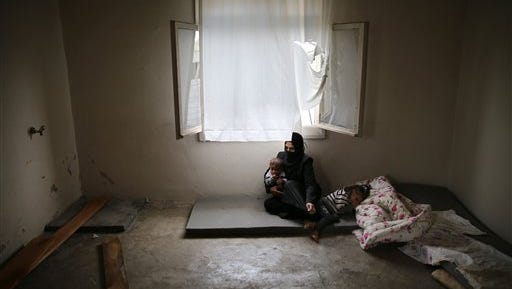"""In this picture from  Oct. 23, 2015, Syrian refugee Hind Salem, 31, who fled Russian air strikes in the  central Syrian town of Palmyra, sits on the ground with her kids at their home in the Turkish-Syrian border city of Reyhanli. """"We had no intention to leave our country at all. But the Russian air strikes made us leave,""""  she said. Other refugees have also waited in Turkey to gain entry into the U.S."""