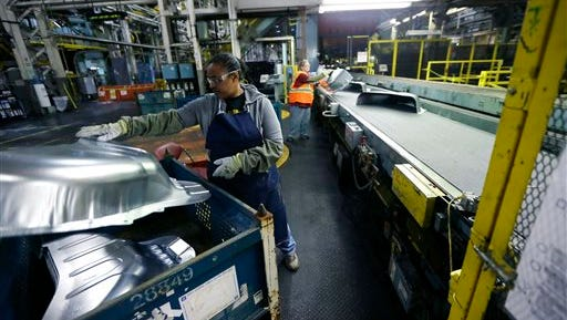 In this April 30 file photo, United Auto Workers line worker Michelle Albritton loads stamped wheel housings at the General Motors Pontiac Metal Center in Pontiac, Mich.