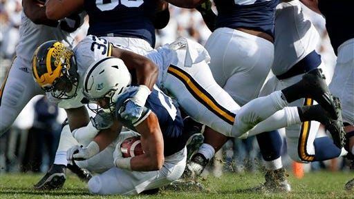 Michigan defensive end Taco Charlton (33) tackles Penn State running back Saquon Barkley (26) in the backfield for a loss on Saturday.