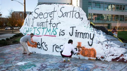 A campus landmark called the Rock is repainted to remove a message calling for the resignation of University of Tennessee Chancellor Jimmy Cheek on Friday in Knoxville. The message alludes to the university's suggestions to faculty and staff regarding office holiday parties, with members of Congress blasting the guidelines as an attempt to enshrine political correctness on campus. The painters declined comment or being identified.