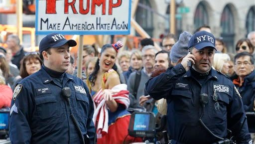 Police officers with the Counter Terrorism unit stand guard as activists protest against Republican presidential candidate Donald Trump outside The Plaza Hotel, where Trump is attending the Pennsylvania Republican party's annual Commonwealth Club luncheon, Friday, Dec. 11, 2015, in New York.