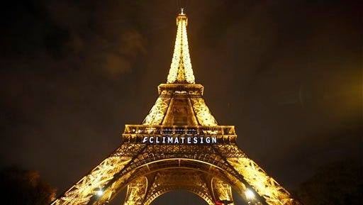 """The slogan """"CLIMATESIGN"""" is projected on the Eiffel Tower as part of the COP21, United Nations Climate Change Conference in Paris, France, Friday, Dec. 11, 2015."""