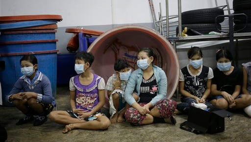 In this Monday, Nov. 9, 2015 photo, children and teenagers sit together to be registered by officials during a raid on a shrimp shed in Samut Sakhon, Thailand. Abuse is common in Samut Sakhon, which attracts workers from some of the world's poorest countries, mostly from Myanmar. An International Labor Organization report estimated 10,000 migrant children aged 13 to 15 work in the city. Another U.N. agency study found nearly 60 percent of Burmese laborers toiling in its seafood processing industry were victims of forced labor.