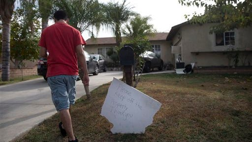 A brother of Enrique Marquez walks back to his house after collecting mail Wednesday, Dec. 9, 2015, in Riverside, Calif. Authorities have said Enrique Marquez, an old friend of San Bernardino attacker Syed Farook, purchased two assault rifles used in last week's fatal shooting that killed 14 people. (AP Photo/Jae C. Hong)
