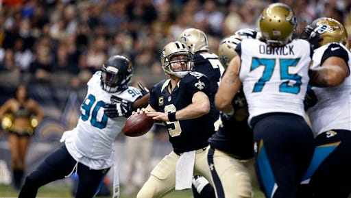 New Orleans Saints quarterback Drew Brees (9) passes under pressure from Jacksonville Jaguars defensive end Jared Odrick (75) in the first half of an NFL football game in New Orleans on Sunday.
