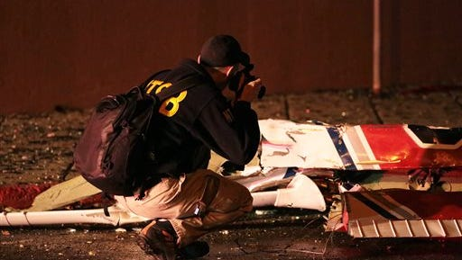 A National Transportation Safety Board investigator takes photos at the scene of an aircraft crash, Tuesday, Dec. 29, 2015, in Anchorage, Ak.  A small plane clipped a downtown Anchorage office building and then slammed into a nearby commercial building early Tuesday, igniting a fire and killing at least one person aboard, authorities said.