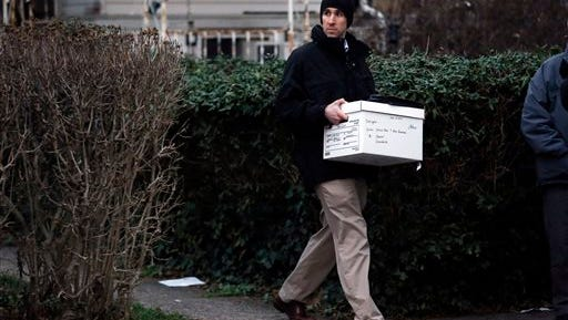 An investigator takes a box from one of the residences where suspect Edward Archer has lived Friday, Jan. 8, 2016, in Yeadon, Pa. Archer accused of ambushing a police officer and firing shots at point-blank range said he was acting in the name of Islam and had pledged allegiance to the Islamic State group, Philadelphia authorities said Friday.