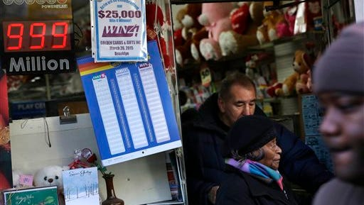 People walk past a sign, left, advertising the Powerball lottery in New York, Monday, Jan. 11, 2016. The jackpot is so big that billboards around the country have to advertise the prize as $999 million because they're not built to show billions. (AP Photo/Seth Wenig)