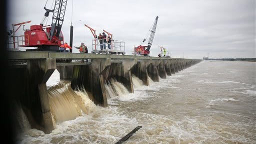 """Cranes atop the weir separating the Mississippi River from the Bonnet Carre Spillway in Norco, La., began pulling long creosoted timber """"needles"""" from the first of 350 bays at about 10:45 a.m. Sunday, Jan. 10, 2016,part of a plan to reduce the river's flow as it moves past New Orleans by directing part of its water into Lake Pontchartrain. (Kathleen Flynn/NOLA.com The Times-Picayune via AP)"""