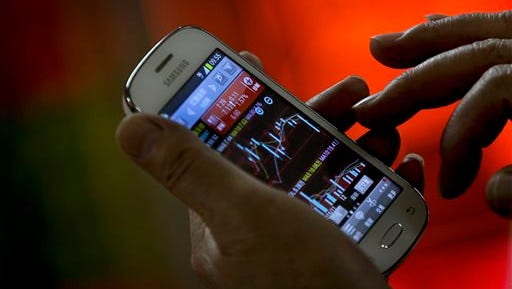 An investor checks stock index through his smartphone at a brokerage house in Beijing, Tuesday, Jan. 5, 2016. Most Asian stock markets inched higher Tuesday as China's benchmark stabilized a day after plunging nearly 7 percent. (AP Photo/Andy Wong)