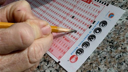 A lottery player fills out numbers on a powerball form Tuesday, Jan. 12, 2016, in Oakland, Calif. The Powerball jackpot has grown to over 1.5 billion dollars.