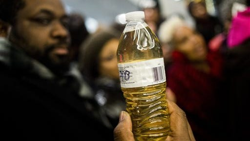 Pastor David Bullock holds up a bottle of Flint water as Michigan State Police hold a barrier to keep protestors out of the Romney Building, where Gov. Rick Snyder's office resides on Thursday, Jan. 14, 2016, in Lansing, Mich. More than 150 people tried to flood into the lobby in protest against Snyder, asking for his resignation and arrest in relation to Flint's water crisis.  (Jake May/The Flint Journal-MLive.com via AP)