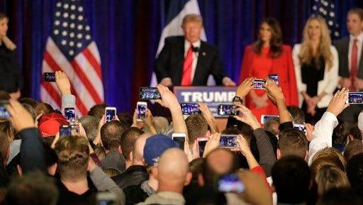 Supporters take pictures as Republican presidential candidate, businessman Donald Trump speaks at his caucus night rally, Monday, Feb. 1, 2016, in West Des Moines.