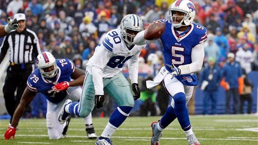 Buffalo Bills quarterback Tyrod Taylor (5) runs with the ball as Dallas Cowboys defensive end Demarcus Lawrence (90) chases after him during a game.
