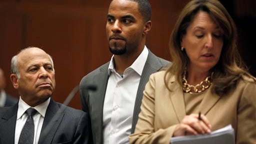 In this file photo, former NFL football player Darren Sharper, center, appears in Los Angeles Superior Court with his attorneys, Blair Berk, right, and Leonard Levine, Friday, Feb. 14, 2014.