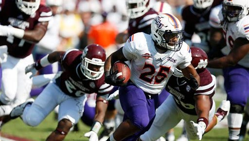 Northwestern State running back De'Mard Llorens (25) runs past Mississippi State defenders during the first half of their game last season.
