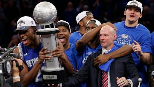 Seton Hall head coach Kevin Willard, right, watches as Myles Carter (23) celebrates with the tournament trophy