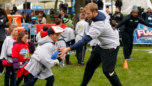 North Dakota State QB Carson Wentz hands off the ball during an NFL Play 60 event in Chicago on Wednesday, one day before the Eagles are expected to make him the second overall pick in the NFL draft.