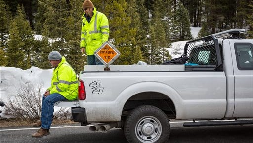 In this Friday, May 20, 2016 photo, crew members prepare to load explosives onto a helicopter to be detonated on a nearby ridge line above Colorado Highway 82 on Independence Pass near Aspen, Colo. Road crews working on Mount Evans won't get the holiday weekend off. The highway to the summit usually opens on the Friday before Memorial Day but the Colorado Department of Transportation says this year the road will only open to Summit Lake on Friday, May 27, because of all the snow that that fell in May. Independence Pass is on track to open Thursday, May 26, its traditional opening day.   (Jeremy Wallace/The Aspen Times via AP) MANDATORY CREDIT