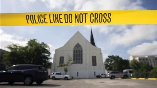 In this Friday, June 19, 2015 file photo, police tape surrounds the parking lot behind the AME Emanuel Church, a predominantly black church, as FBI forensic experts work at the crime scene where nine people where shot by white suspect Dylann Storm Roof, 21, on Wednesday in Charleston, S.C. The FBI collects extensive data on hate crimes each year, but nearly 2,800 local law enforcement agencies are not submitting the information, according to an investigation of 2009-2014 data by The Associated Press. Thousands more file reports with the FBI only sporadically.