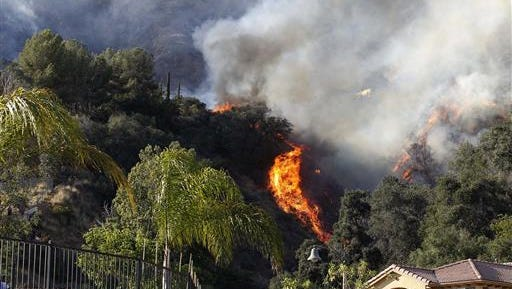 A wildfire burns around homes built near a hilltop in Azusa, Calif., Monday, June 20, 2016. New wildfires erupted Monday in Southern California and chased people from their homes as an intensifying heat wave stretching from the West Coast to New Mexico blistered the region.