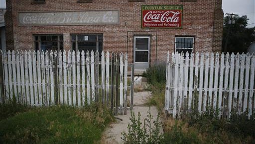 In this July 1, 2016 photo, weeds grow around an old building and picket fence in Rocky Ford, Colo., in Otero County, a rural and increasingly impoverished part of southern Colorado. Two different economic worlds are writ large in this state. It is among those with the greatest economic gap between urban and rural areas, according to an Associated Press review of Economic Innovation Group data.