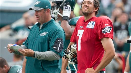 Eagles quarterback Sam Bradford, right, looks on while  coach Doug Pederson calls a play during training camp.