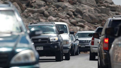 In this Friday, July 15, 2016, photograph, traffic is backed up both going up and down the Mount Evans Scenic Byway just below the summit of Mount Evans near Idaho Springs, Colo. It might seem like every other person in Colorado is hiking a fourteener on any given summer Saturday. While it might not actually be that crowded, the state's highest peaks do count about 260,000 summit-scrambling trips every year. (AP Photo/David Zalubowski)
