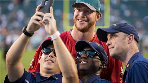 Eagles quarterback Carson Wentz takes a photo with members of the Coast Guard as the Eagles celebrate Military appreciation day Sunday. Wentz has broken ribs and can't practice.