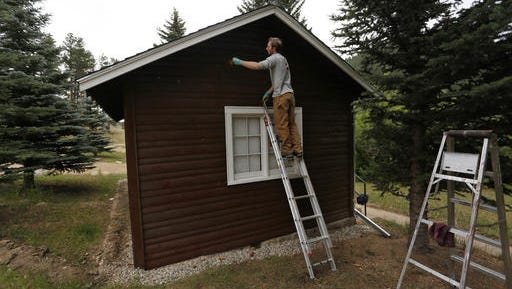Will Fazio, a crew member for the non-profit organization Rocky Mountain Conservancy, helps restore old cabins used by research scientists inside Rocky Mountain National Park, near Estes Park, Colo., on Aug. 4, 2016. Rocky Mountain Conservancy works for the U.S. Park Service, running crews who do whatever work is needed. (AP Photo/Brennan Linsley)