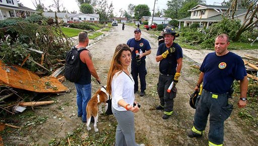 Grey and Spring Rogers talk to Kokomo firefighters while trying to find their 9-year-old son who never came home from school after tornadoes ripped through Kokomo, Ind., Wednesday, Aug. 24, 2016. Multiple tornadoes touched down in central Indiana on Wednesday, tearing the roofs off apartment buildings, sending air conditioners falling onto parked cars and cutting power to thousands of people. (Tim Bath/The Kokomo Tribune via AP)