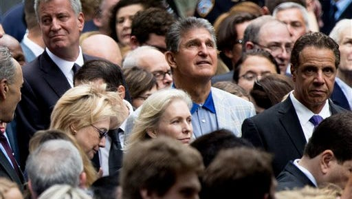 Democratic presidential candidate Hillary Clinton, center left, accompanied by New York Mayor Bill de Blasio, top left, Sen. Kirsten Gillibrand, D-N.Y., center bottom, Sen. Joe Manchin, D-W.Va., center top, and New York Gov. Andrew Cuomo, right, speaks with someone in the crowd as she attends a ceremony for the 15th anniversary of the attacks of the World Trade Center at the National September 11 Memorial, in New York, Sunday, Sept. 11, 2016.