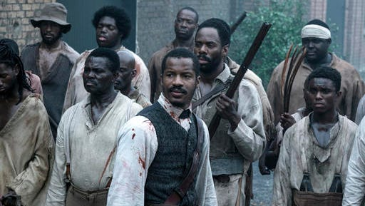 """This image released by Fox Searchlight Films shows Nate Parker as Nat Turner, center, in a scene from """"The Birth of a Nation."""" (Jahi Chikwendiu/Fox Searchlight via AP)"""