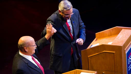 Democrat John Gregg, Republican Lt. Gov. Eric Holcomb high five while participating in a debate for Indiana governor at the University of Southern Indiana in Evansville, Tuesday, Oct. 25, 2016. (AP Photo/Alex Slitz, Pool)